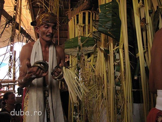 """Balianii (shamanii) cheama spiritele stramosilor la ceremonie pentru a le multumi lor pentru asigurarea bunastarii comunitatii. Kinsai (inelele din mana) sunt pline cu bile din metal si agitate fac un sunet asemantor cu al shakerelor din muzica latino. Fara sunetul lor chemarea balianilor nu este auzita de spirite. In dreapta se vede o parte din """"tiangul babuah"""" sau """"sanggar"""" un stalp acoperit cu frunze de palmier (arin), prin inetrmediul caruia sunt contactate spiritele."""
