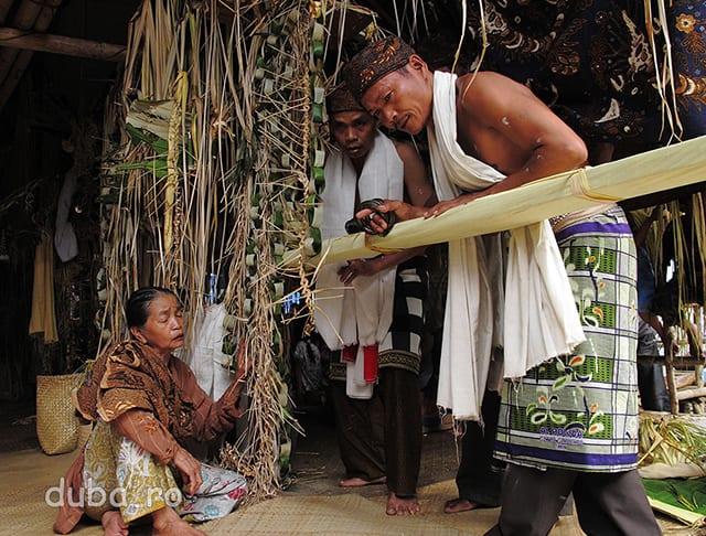 Patati (femeia saman) cu mana pe frunzele de arin (un palmier - mediul de comunicare cu zeii si starmosii) le transmite samanilor-dansatori unde sa duca ofrandele. Ei folosesc limba halong-kuno, o varianta arhaica a limbii tribului dayak din aceasta zona.