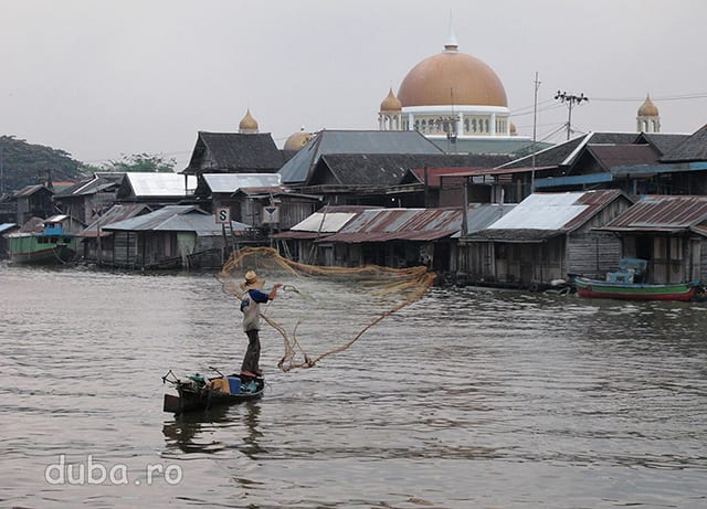 Dupa ce piata se linisteste un pescar iese la aruncat plasa. In spate se vede moschea mare din Negara.