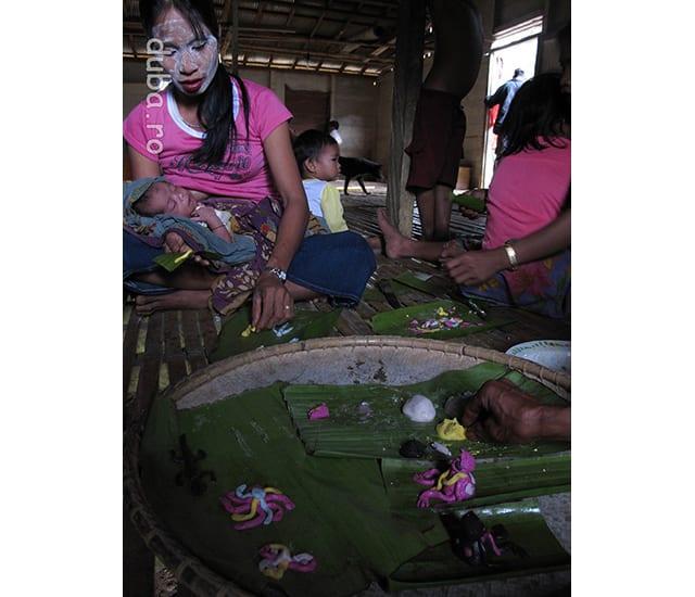 In pregatirea ceremoniei, femeile fac diverse figurine din faina de orez cu coloranti. Oameni in diverse pozitii (roz si negru, dreapta imaginii) reprezinta multumirea pe care o aduc zeilor pentru ca au fost scapati de boli si probleme. Cineva bolnav care cere ajutorul zeilor, dupa vindecare le multumeste prin intermediul unei miniaturi a sa. Crocodili (stanga) - oamenii ii asigura pe crocodili si alti monstri ca toti pot trai in pace, astfel incat crocodilii sa nu-i deranjeze pe oameni. Libelula (floarea din stanga) - ea va purta mesajul de pace al comunitatii catre celelalte fiinte.