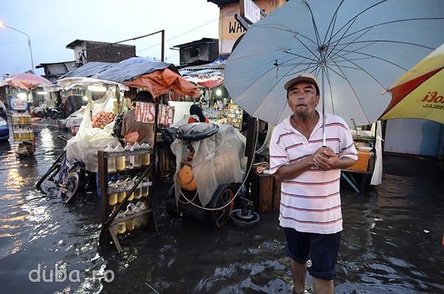 Un vanzator de benzina asteapta cumparatorii. In Surabaya o ploaie torentiala a inundat strazi intregi, ceva de asteptat in sezonul ploios. In dreapta vanzatorului e raftul cu sticlele de benzina, cum se gasesc pe toate strazile mari, pentru milioanele de scutere care in metropolele de aici zumzaie zi-lumina.