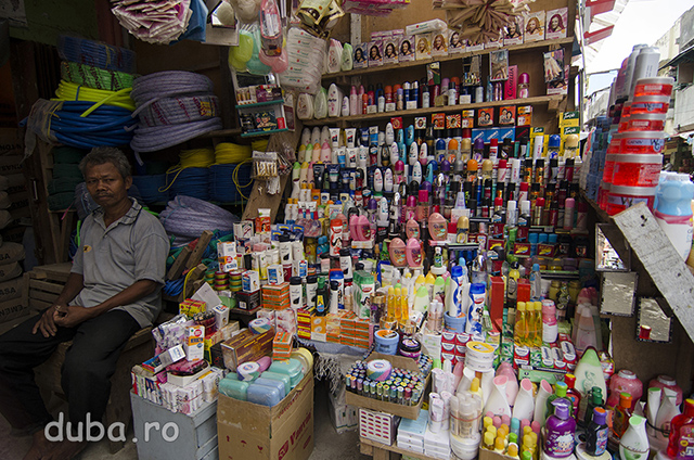 Un vanzator de cosmetice si materiale de constructii, in bazarul din Batu Merah vinde de la saci cu ciment (capetele sacilor din stanga) la gel de par (borcanele din dreapta).