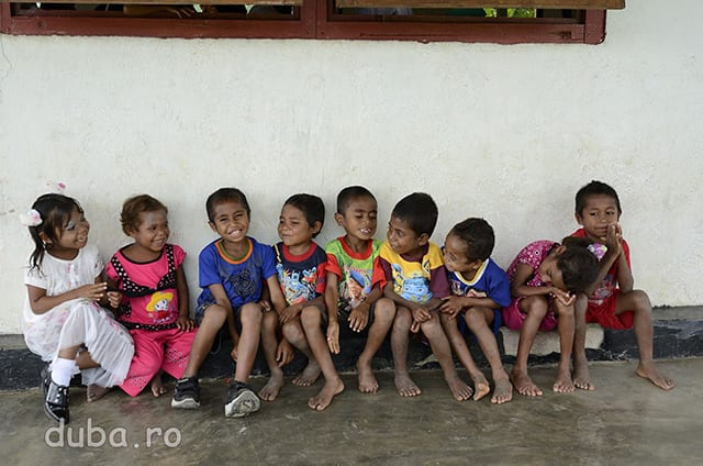 Niste copii din Manusela asteapta afara incheierea slujbei.