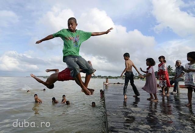 La pontonul din Bula o gramada de copii fac concurs de sarituri. Peliacula de petrol de pe mare nu le afecteaza distractia insa le da batai de cap parintilor lor care obisnuiau sa pescuiasca aici.