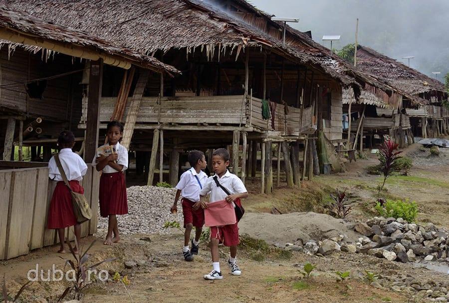 Dimineata, copiii din Huaulu se duc spre scoala, imbracati in uniformele pentru ciclul primar.