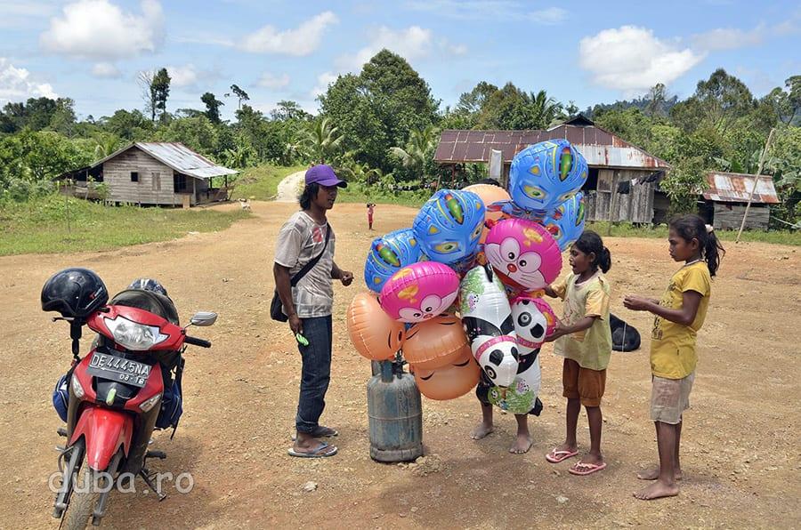 Un vanzator ambulant descaleca cu baloane si alte jucarii, in partea de jos a satului. In 2010, pentru construirea scolii, Huaulu a fost legat de soseaua de coasta cu un drum de masina (in planul din spate al imaginii). Inainte, Huaulu era accesibil doar pe o poteca de picior, prin padure. Acum, drumul cel nou, aduce in sat tot mai multi vanzatori cu bunuri de la oras.