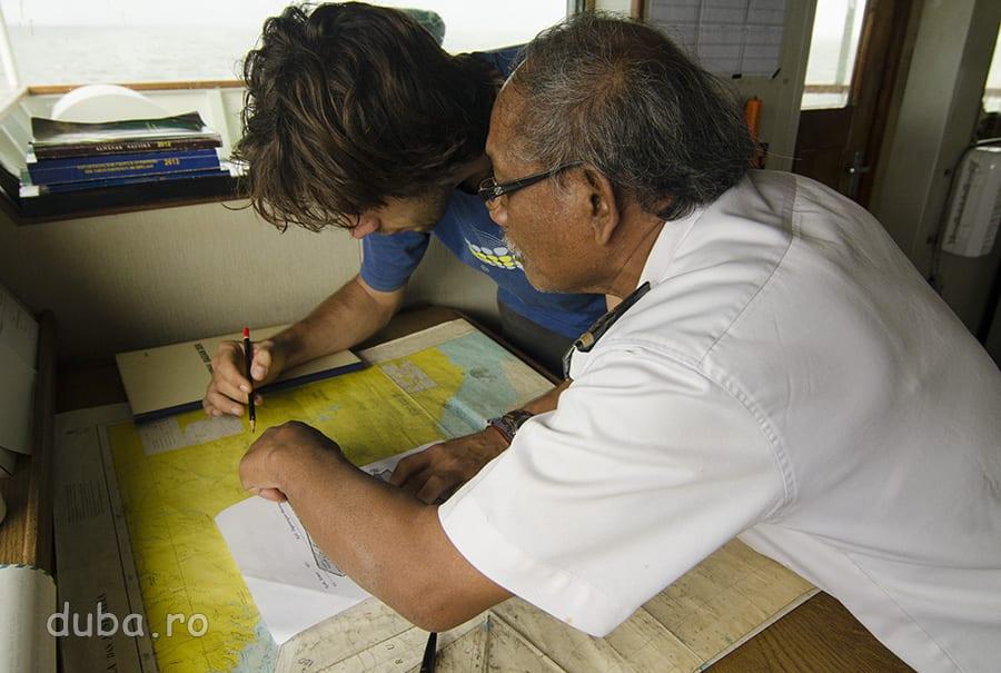 In cabina Tatamailau, Iulius ia notite de pe hartile cu cursurile de apa, de deasupra zonei Asmat.