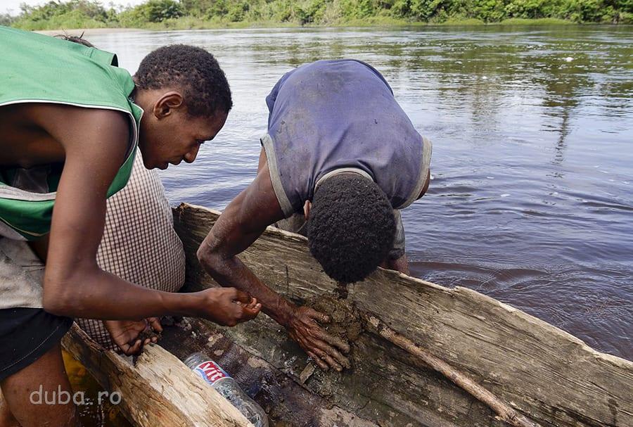 Verii lui Gohon cârpesc canoea, cu pământ, înainte de a pleca spre Yaniruma. Când mi-au dat un boț de noroi argilos, să mai astup găurile bărcii din mers, am fost sceptic. Mi-am pus aparatul foto în două rânduri de pungi. Dar, apoi, am văzut că funcționează.