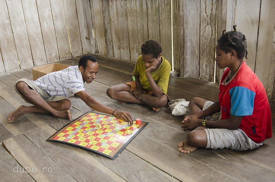 La școală. Fetele învăță să numere folosind un joc, care implica număratul, de la 1 la 100. În stânga este învățătorul, un korowai pe care Peter, misionarul, l-a luat dintre copaci și l-a școlit. După ce a terminat școala, jos la oraș, s-a întors în Senimburu, să-i învețe carte și pe alții.